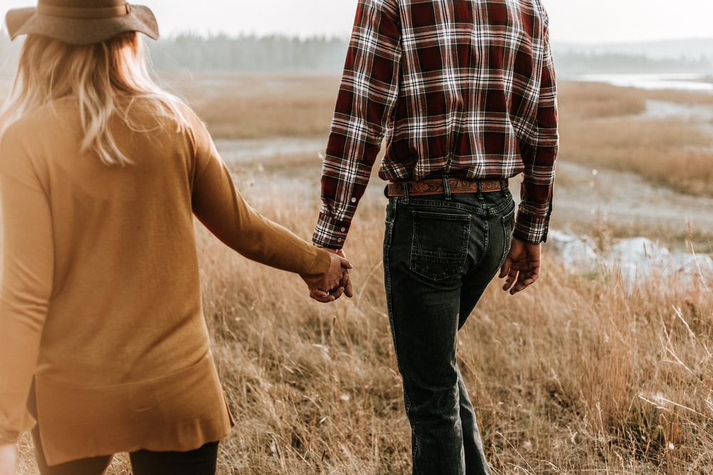 man and woman walking along grass field while holding hands