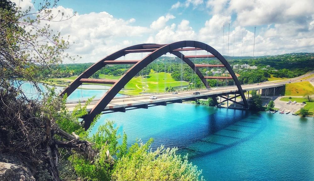 concrete bridge above calm body of water
