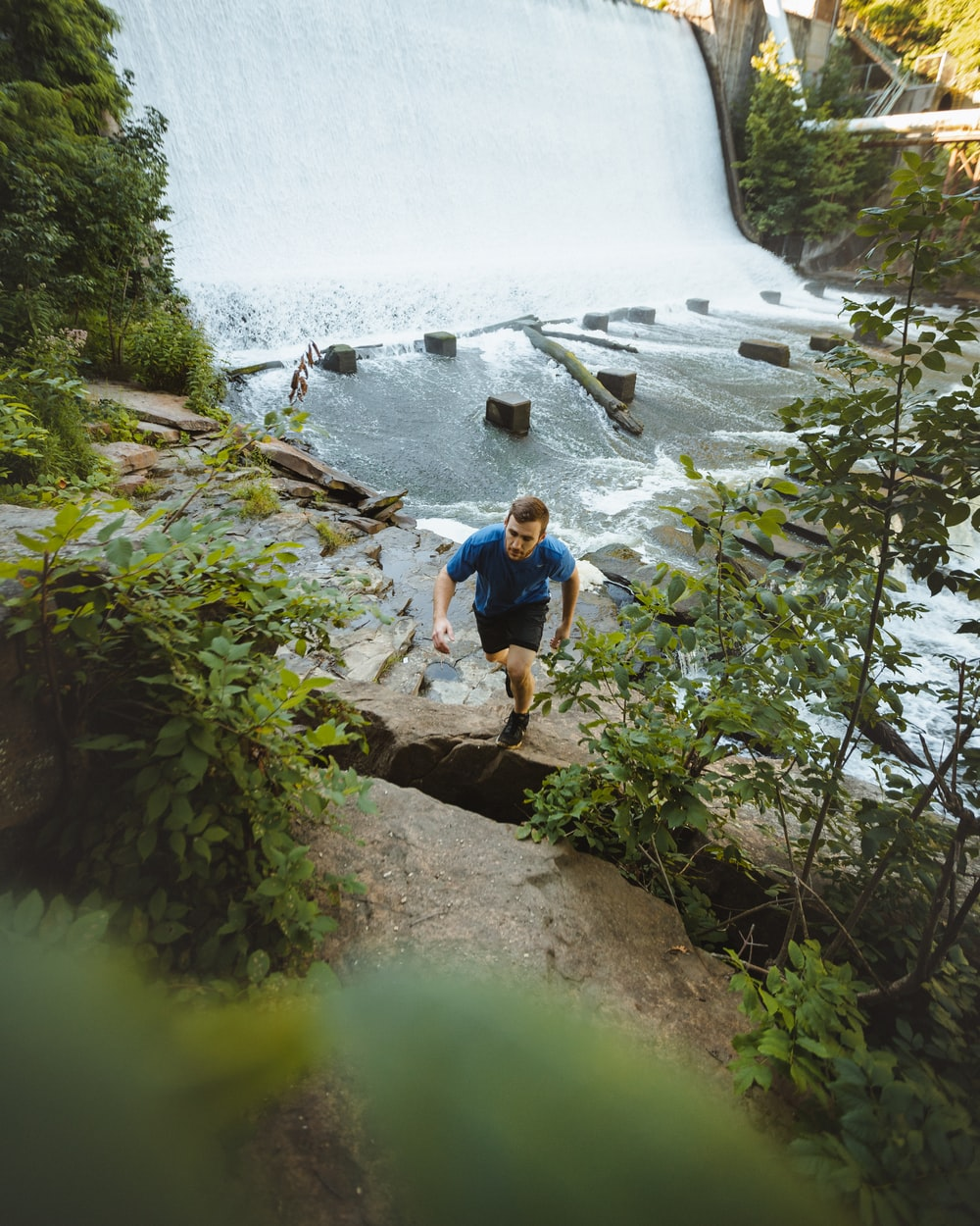 man climbing on cliff beside river