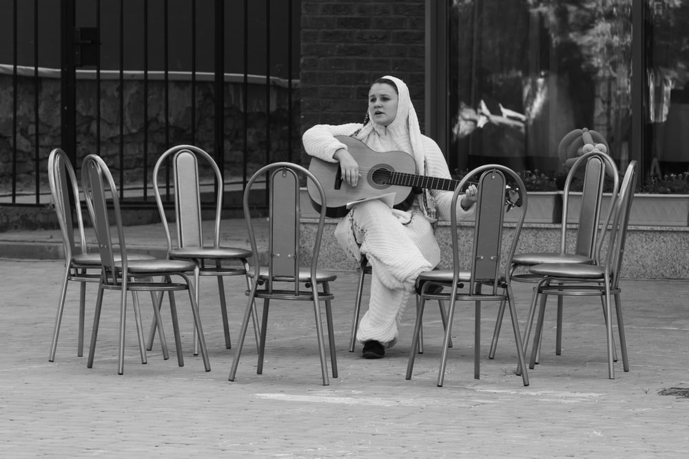 grayscale photography of woman playing guitar