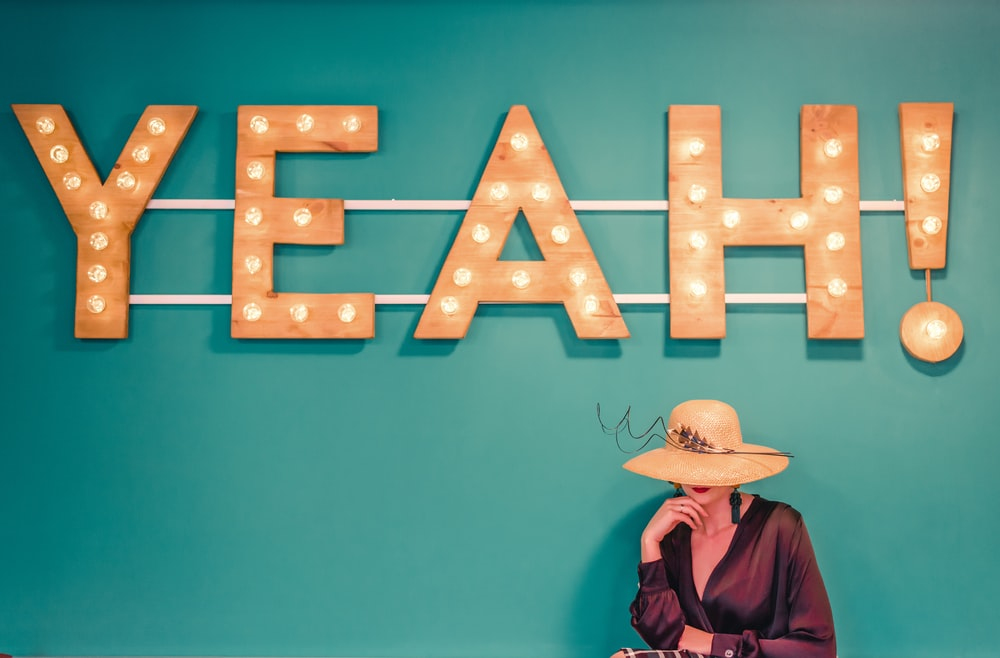woman wearing brown hat near the yeah signage photography