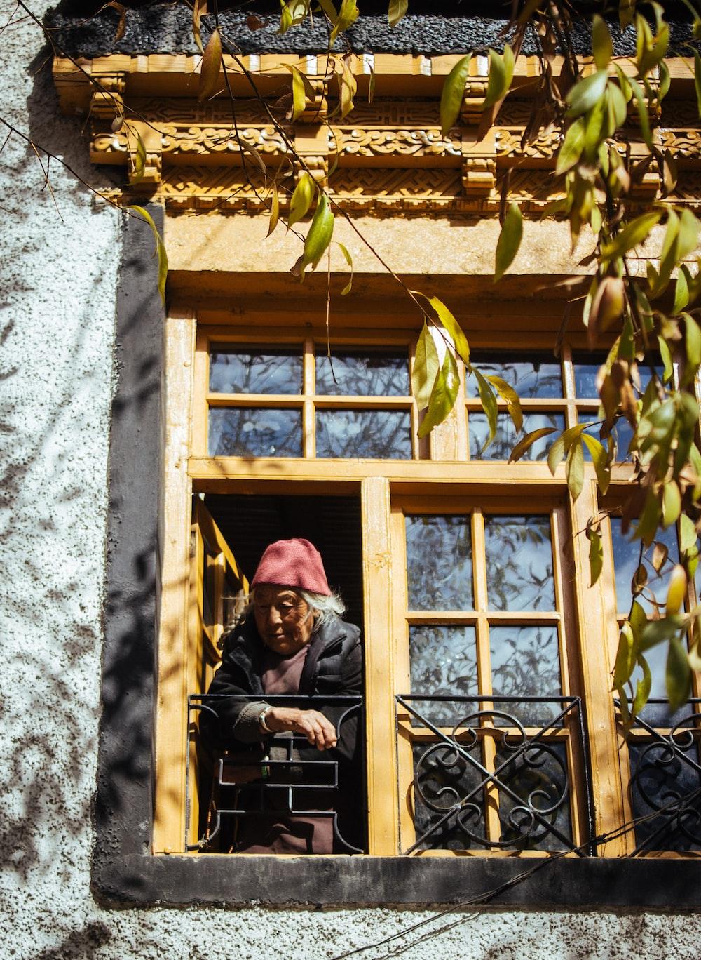 woman standing open window