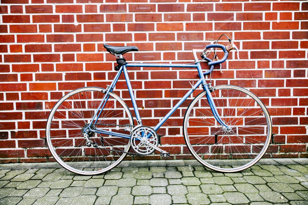 blue road bike leaning on wall