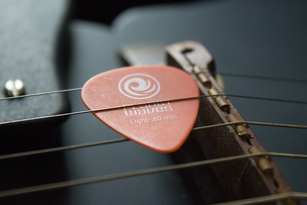selective focus photography of brown guitar pick on guitar strings