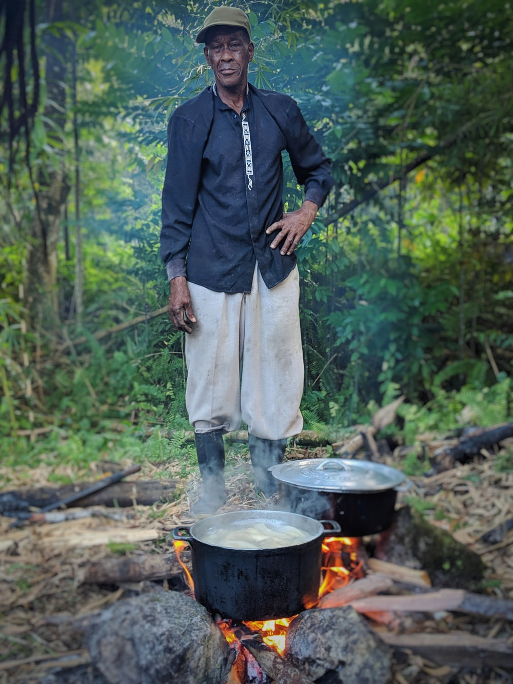 man standing in front of cooking pots