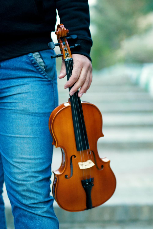man holding brown violin