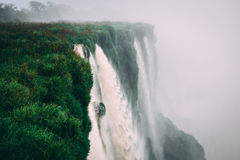 water falls with green field under foggy weather