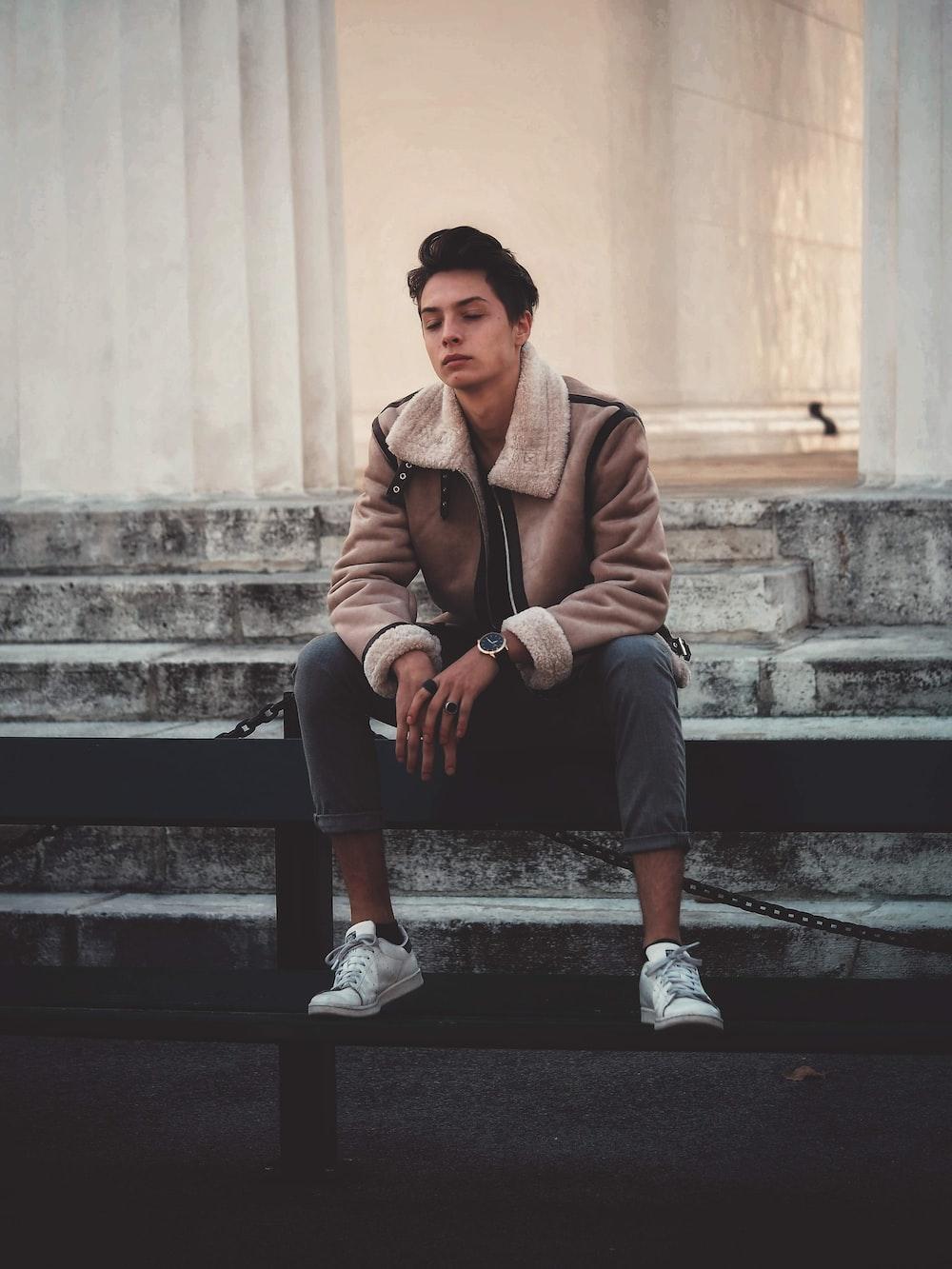 man wearing brown jacket sitting on fence