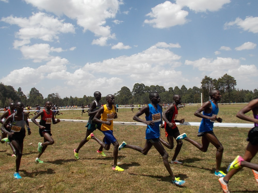 group of men running on field