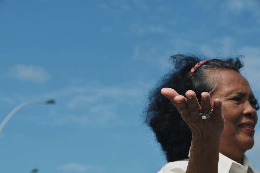 woman wearing white collared shirt under blue sky during daytime