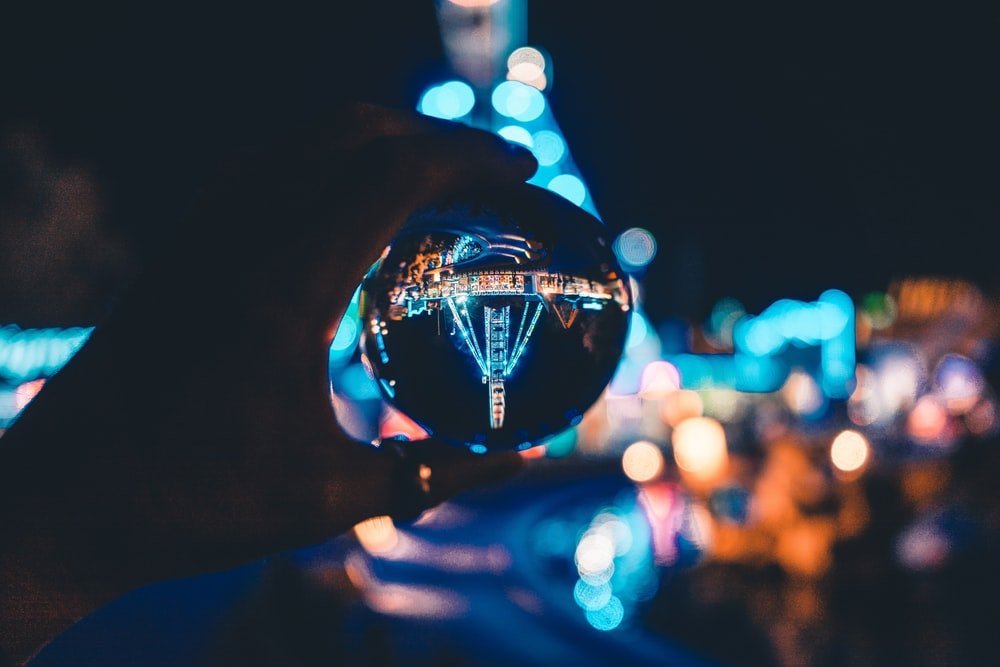 macro photography of person holding glass ball