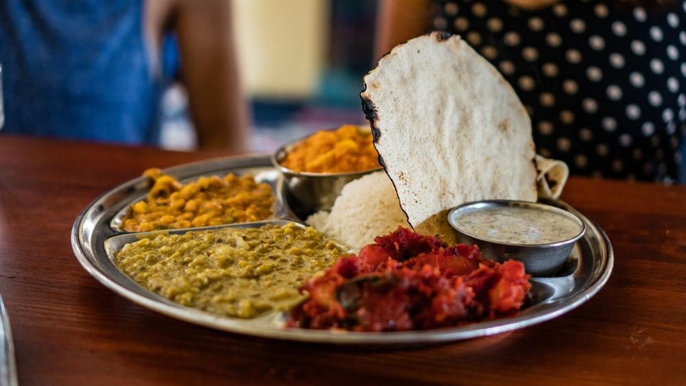 flatbread beside steam rice and stew meat platter