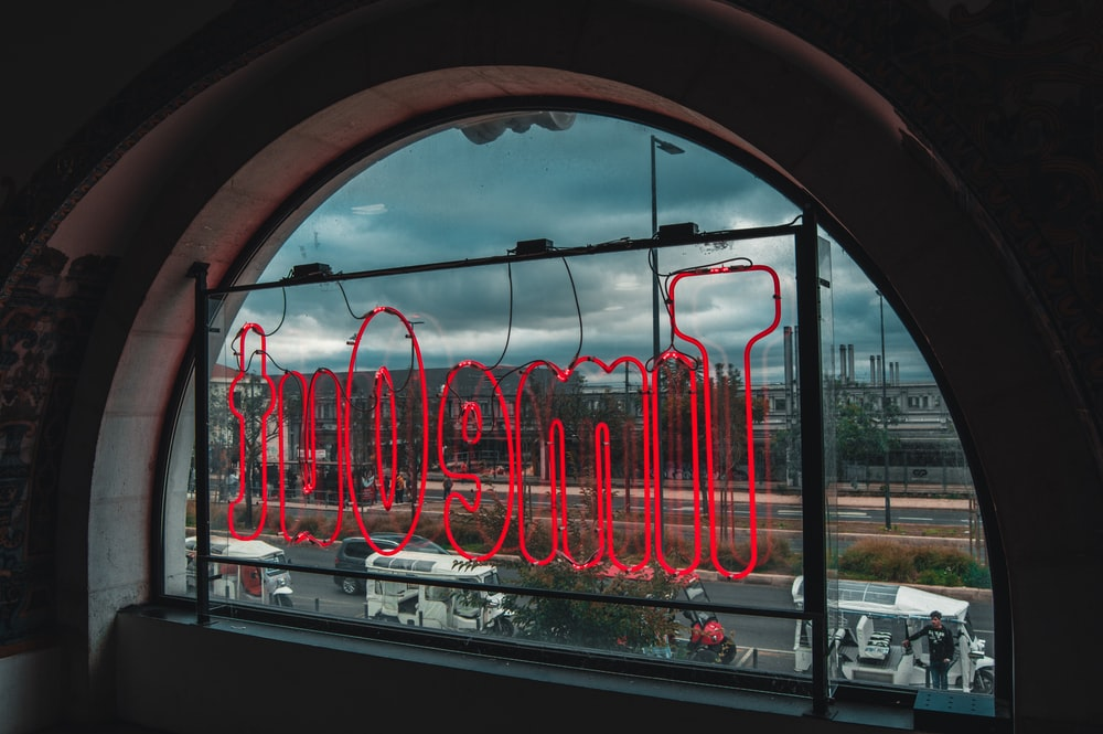 red neon signage placed on window panel