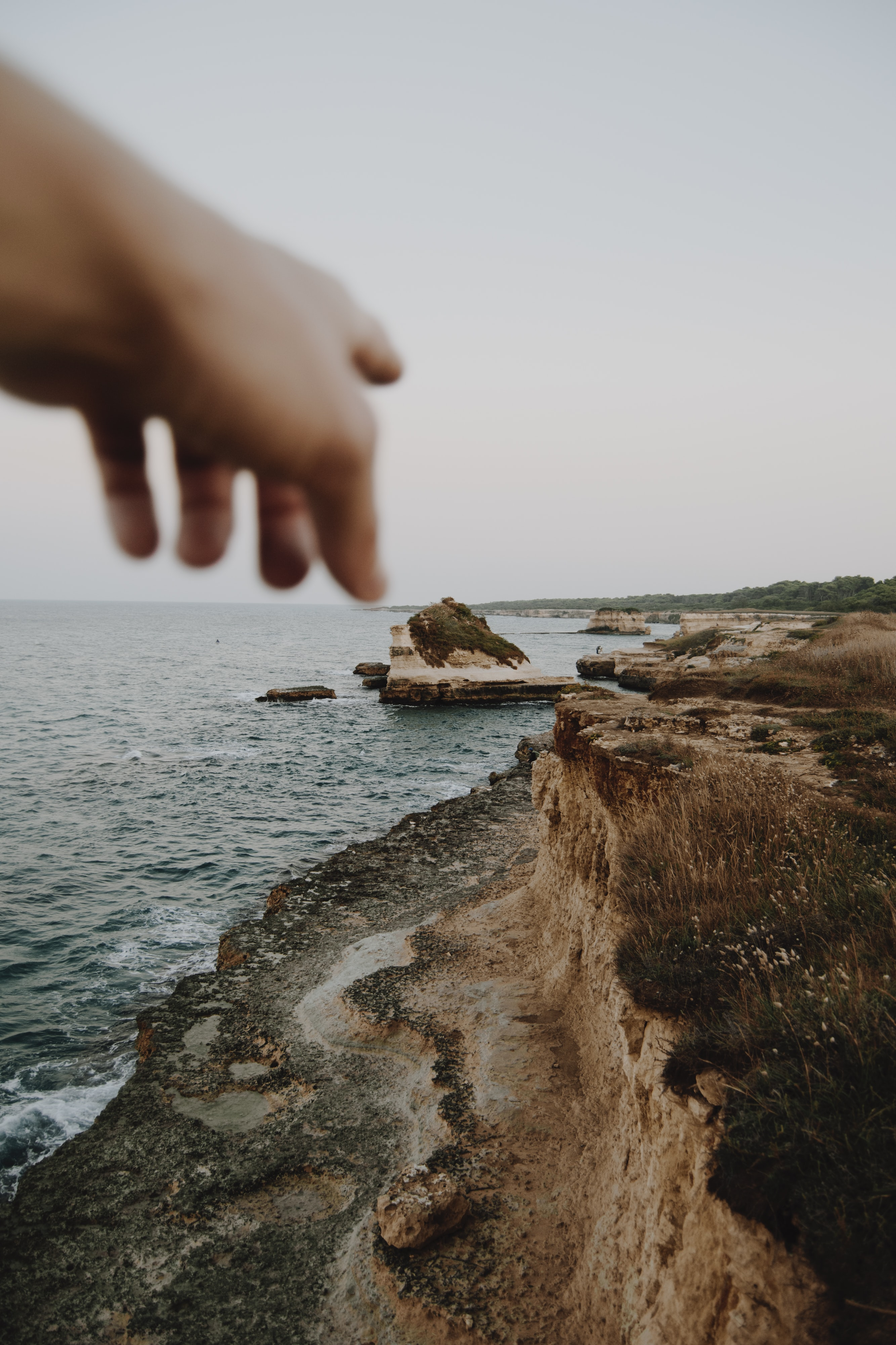 person pointing seashore