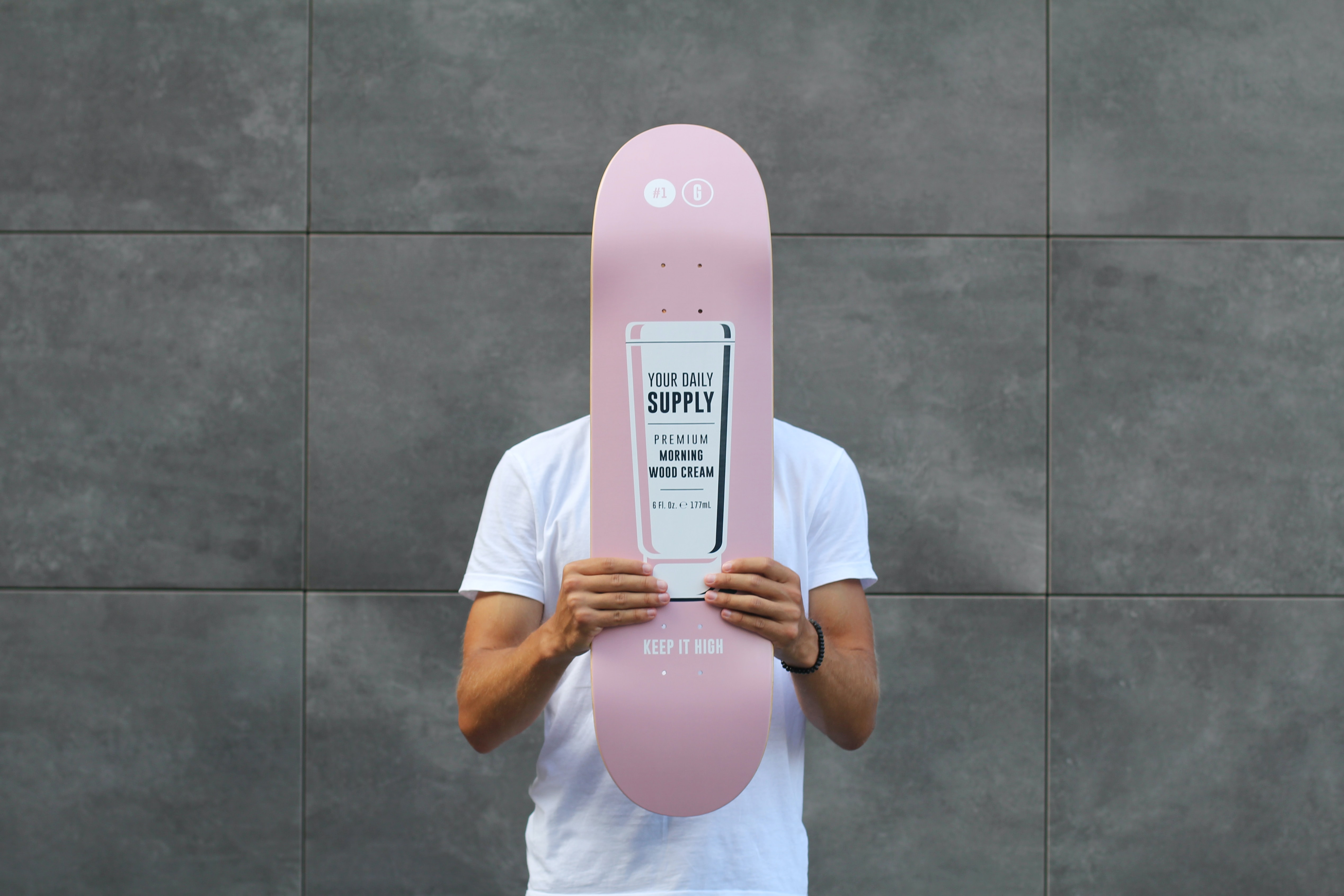 man holding a pink board over his face