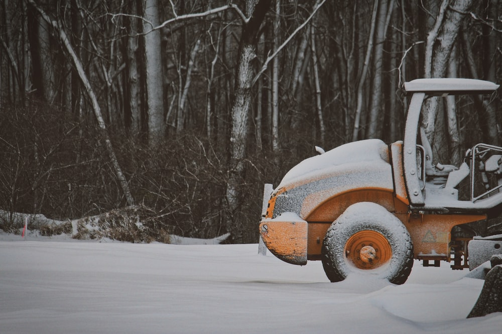 yellow truck covered with snow near trees