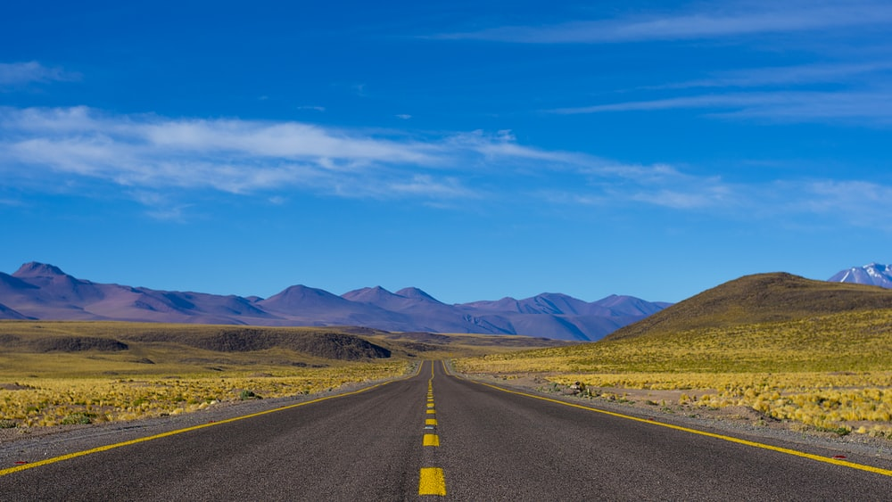 empty paved road near mountains during daytime