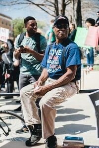 """3/29/18: University of North Texas students gathered at the Library Mall in Denton, Texas after word spread that a small group of Nation Street Preacher demonstrators were there to """"outreach"""" with their racist, anti-gay rhetoric. Counter-protesters held signs, danced, chanted and played instruments to drown out the slurs from the preachers' megaphone. Counter protesters included Christians, BLM activists and the LGBTQIA community, all joined together to denounce the unwelcome messages. This older gentleman looked on the student's counter protest with pride."""