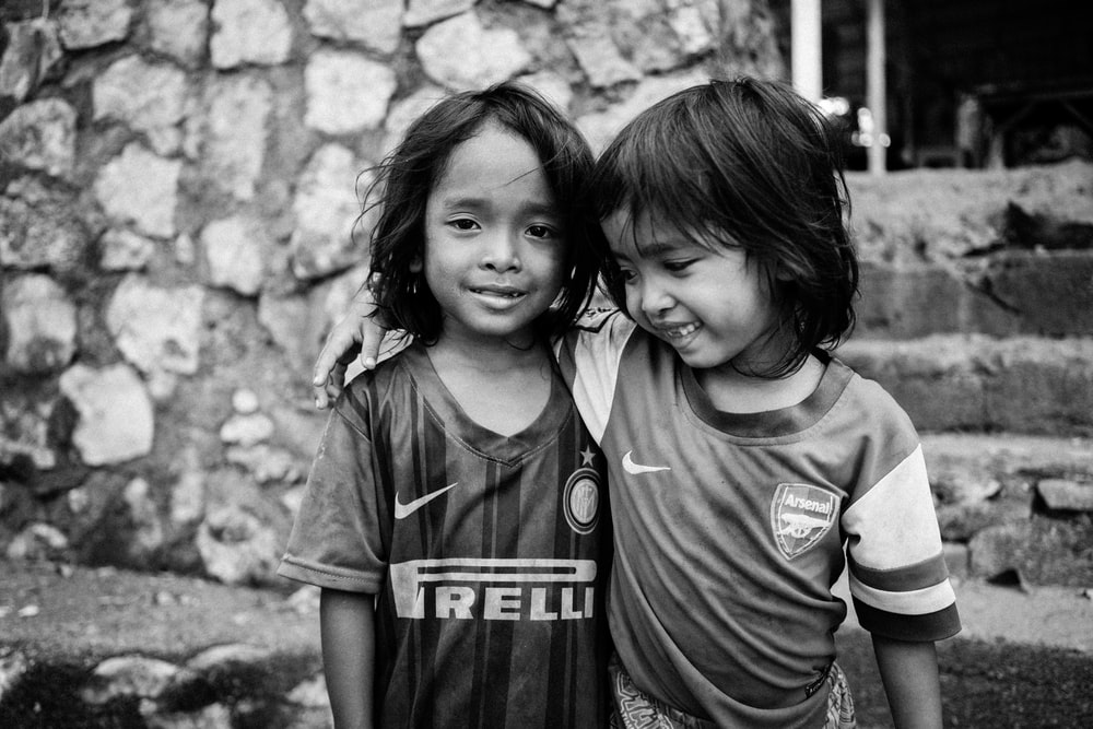 smiling girl putting hand on shoulder of another girl