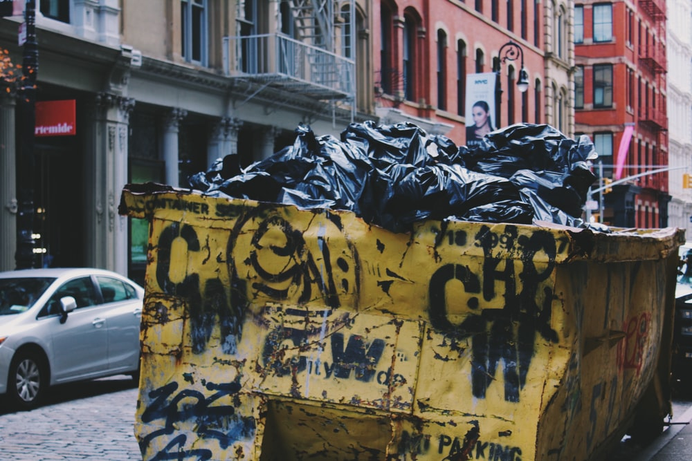 yellow garbage container near silver sedan during daytime