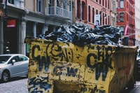 yellow garbage container near silver sedan during daytime