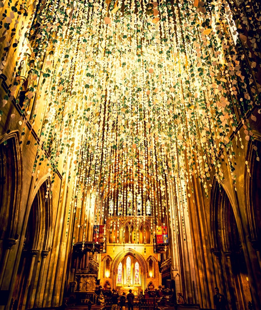 yellow string lights hangs from church ceiing