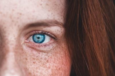 person's blue eye eye teams background
