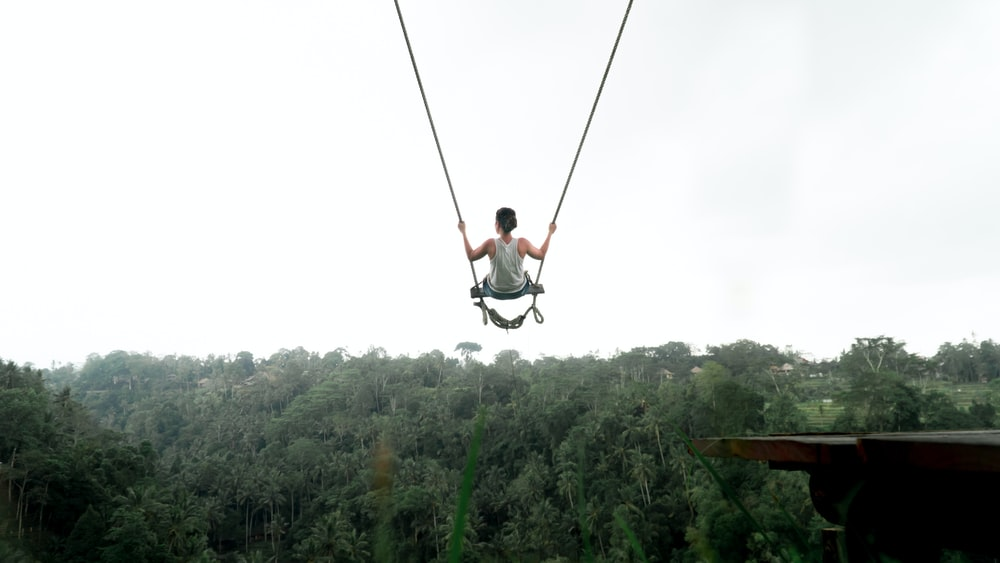 person riding on swing during daytime