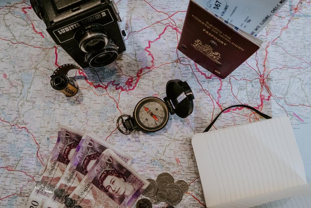 black pocket watch beside banknotes