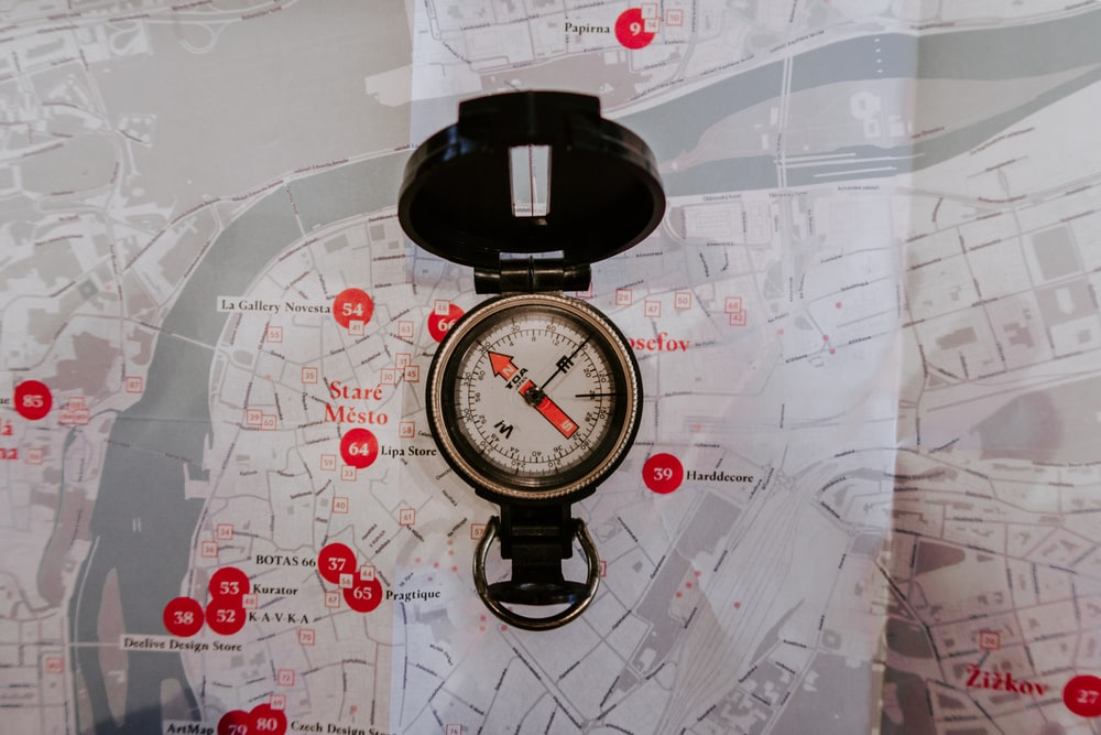 round black metal compass on map