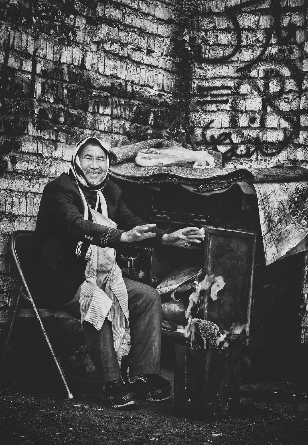 This kind man was sitting at the corner of the street Despite the cold and hard work, he still had a beautiful smile on his lips .