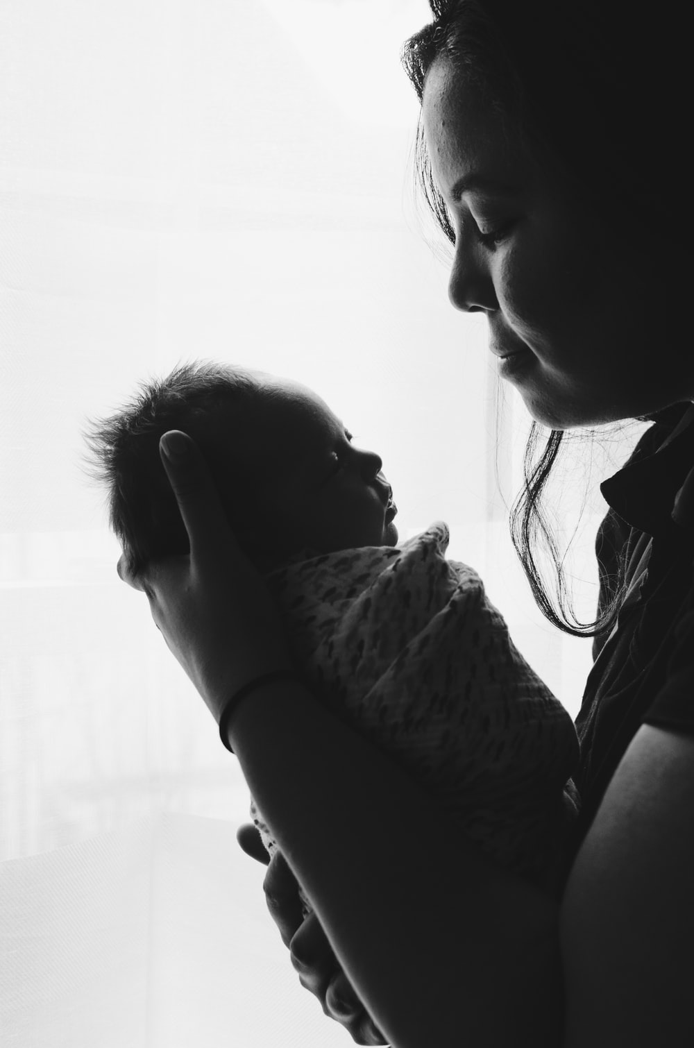 grayscale photography of woman carrying a baby
