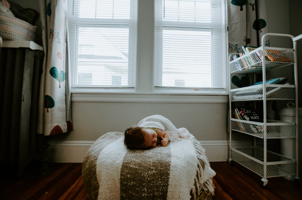 baby sleeping on gray and white bed