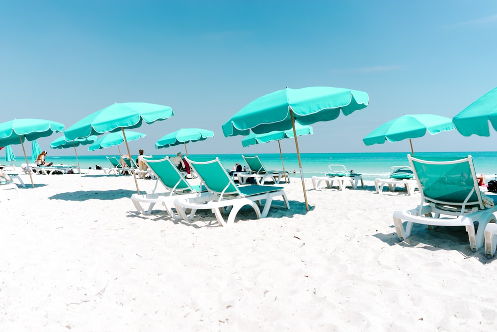 white and green lounger and canopy umbrella in the beach during daytime