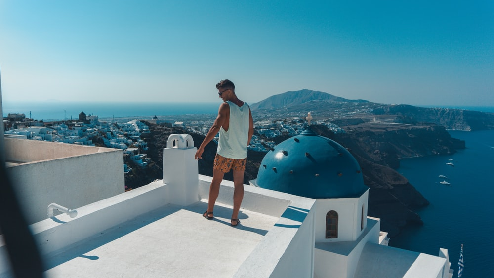 man standing on top of Santorini Greece