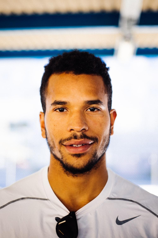 smiling man in white Nike shirt