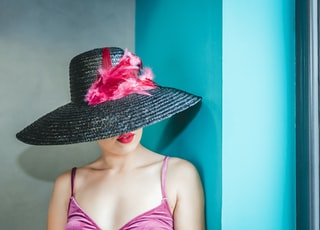 woman wearing pink camitop and black straw hat