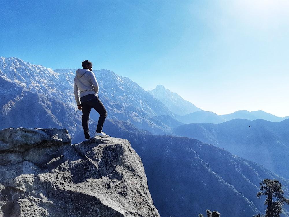 man standing on peak near mountains at daytime