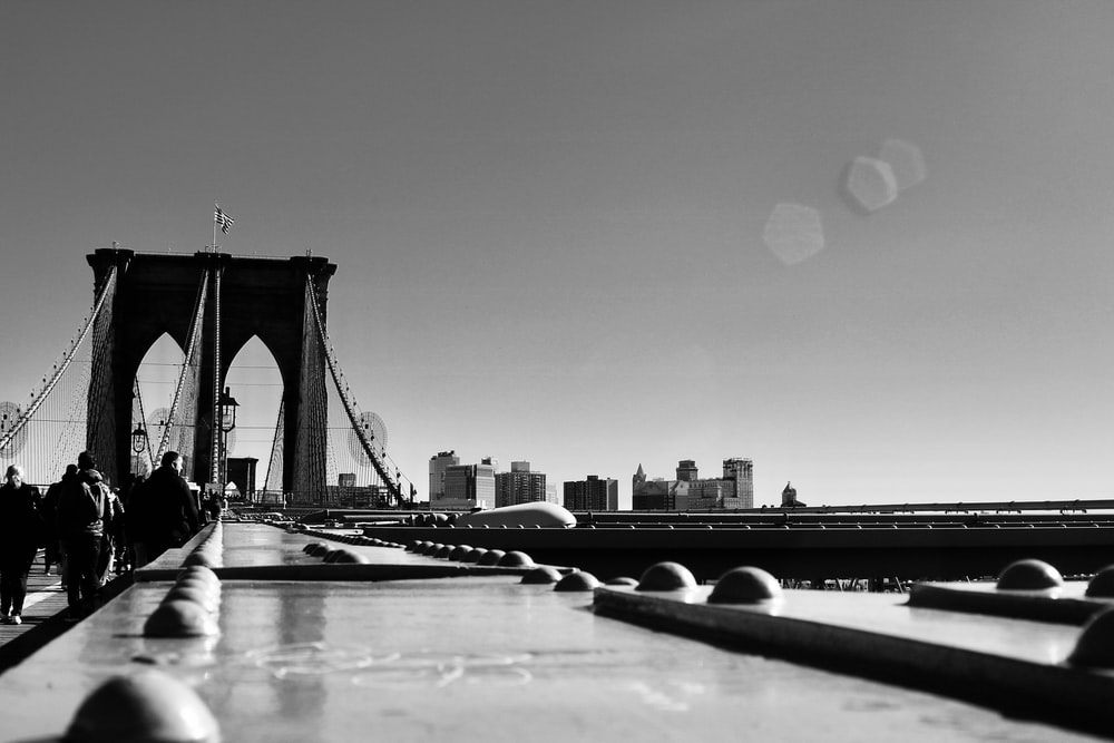 grayscale photography of people walking on Brooklyn Bridge