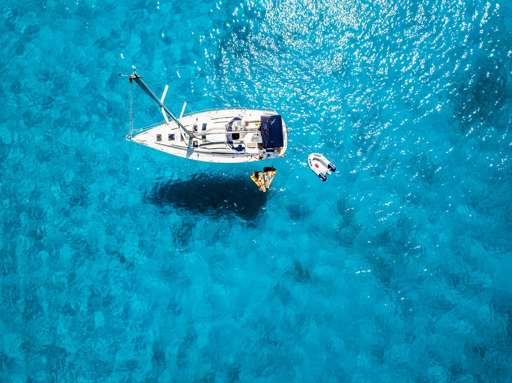 white yacht in middle of blue sea