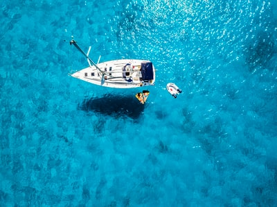 white yacht in middle of blue sea boat teams background