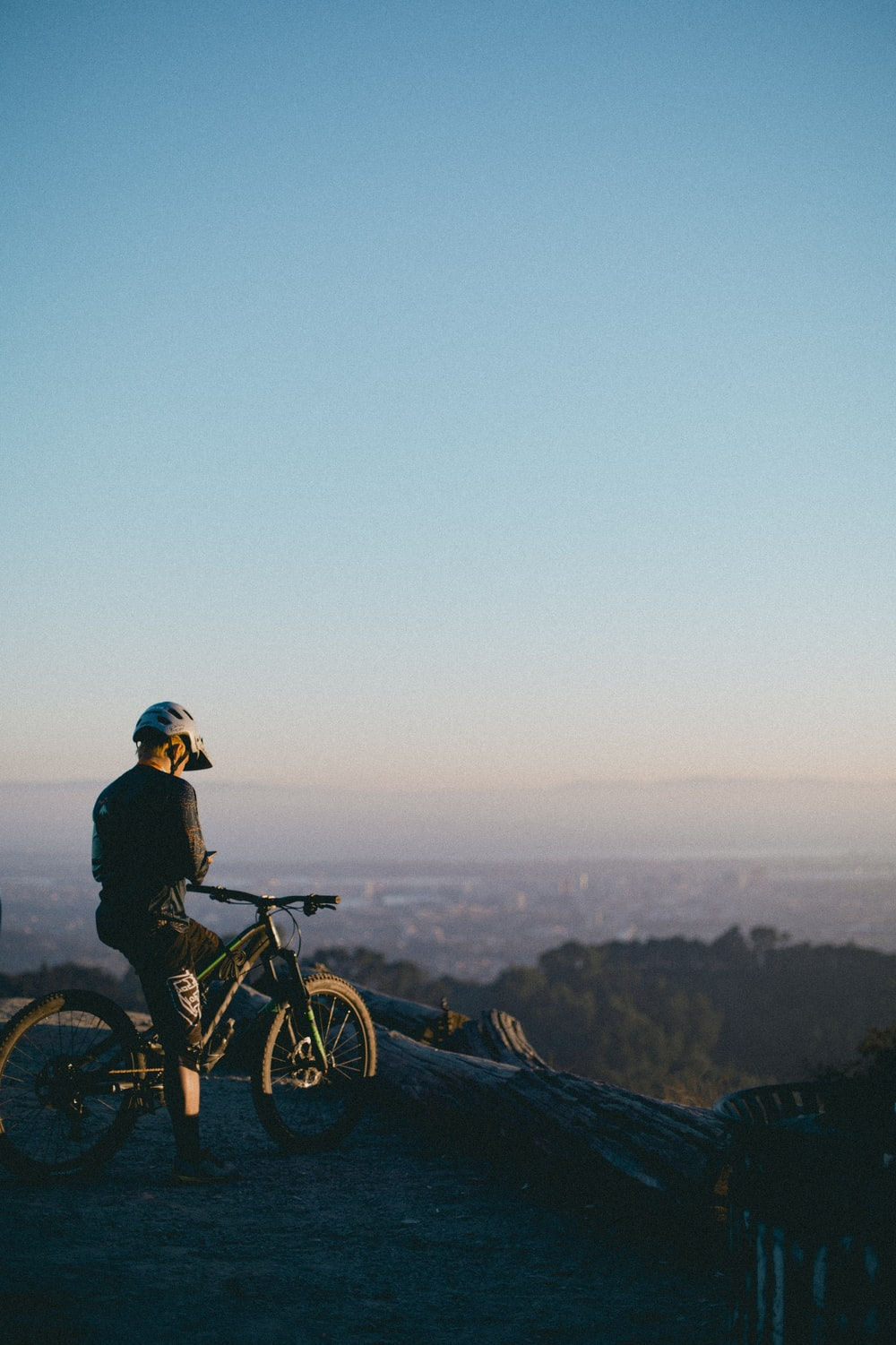 man riding on bicycle while standing on peak