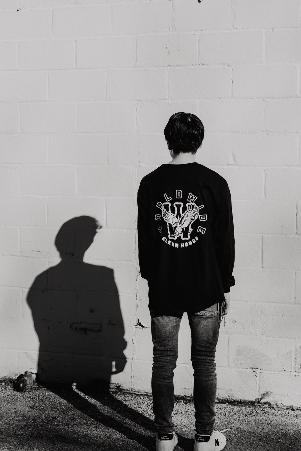 man standing and facing back near wall