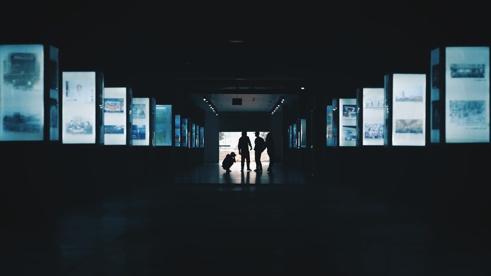 silhouette photography of three person standing in building interior