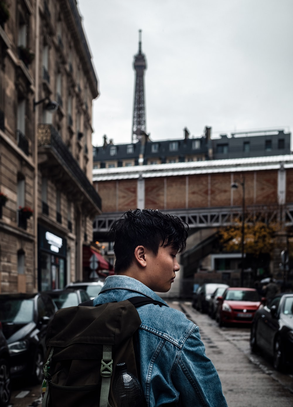 man wearing blue jacket near the building