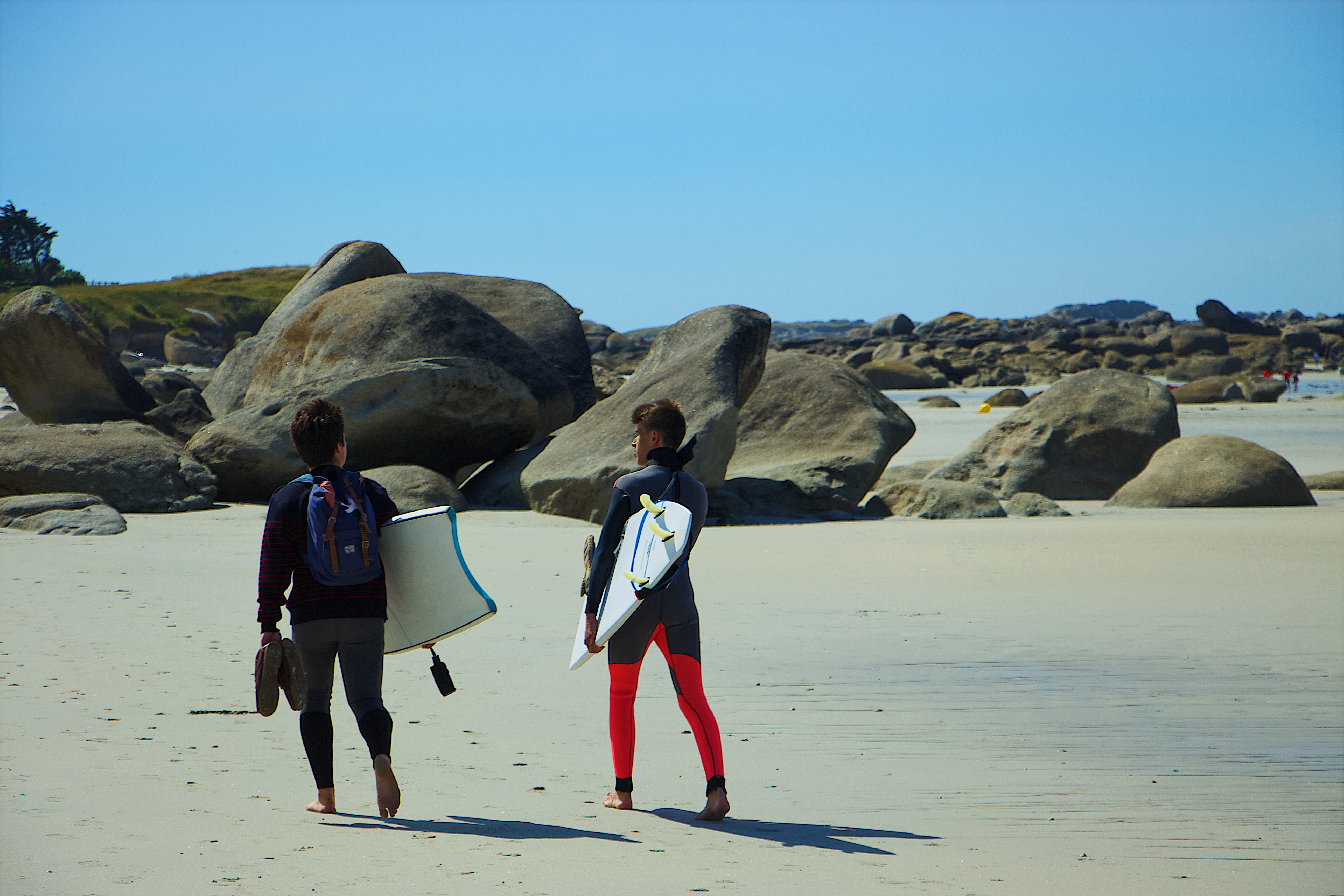 two person with surfboards walking on seashore