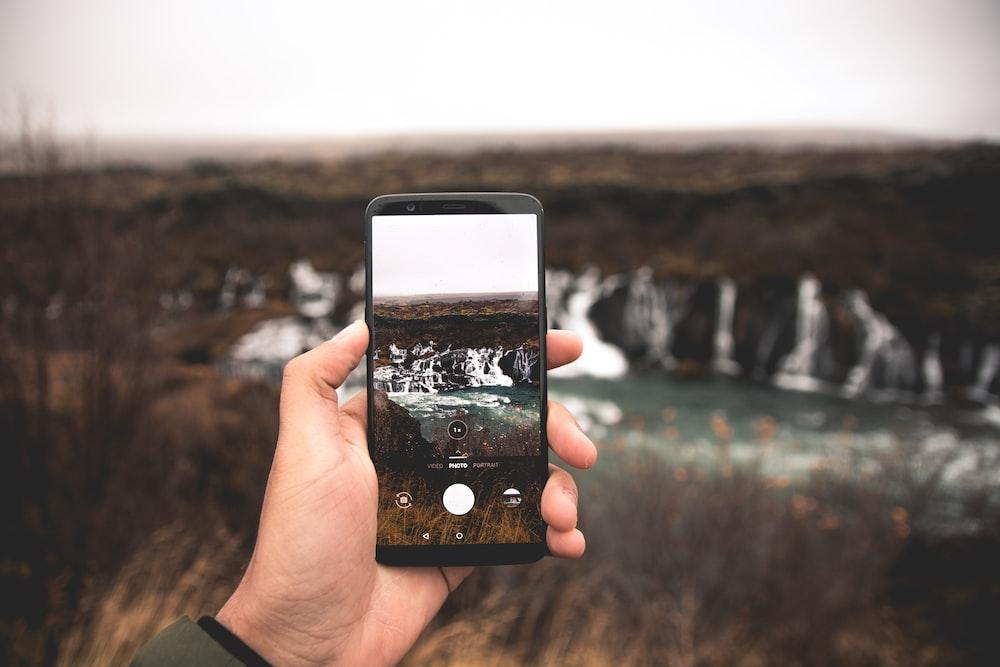 person using black smartphone taking photo