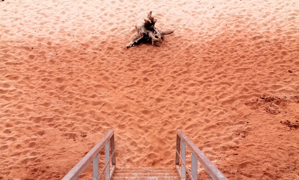 brown wooden stairs near brown sand