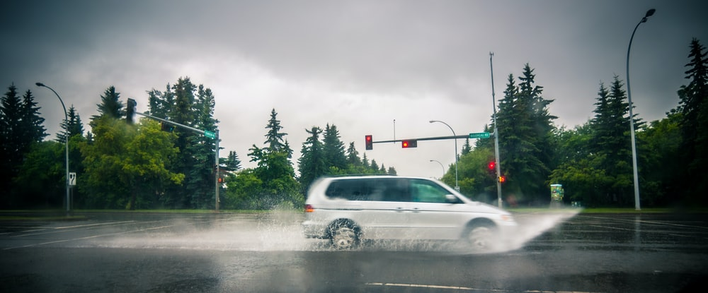 white minivan on road with water splash