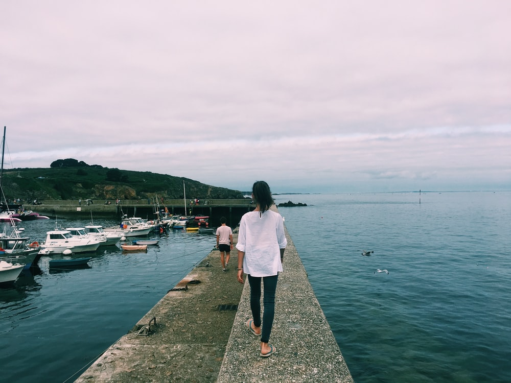 woman walking on dock with boats on the side